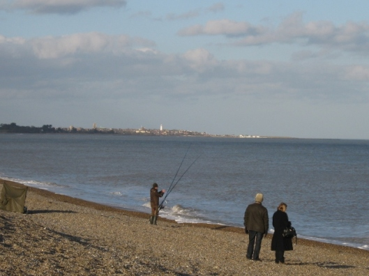 022Fisherman on Dunwich beach with Southwold in the distance (640x480)